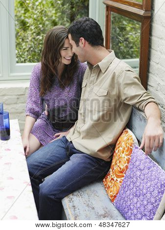 Young romantic couple sitting at verandah table