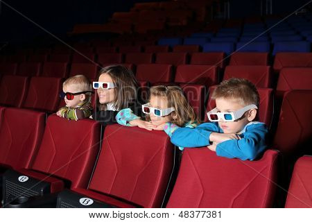 Mother with their children watching a movie in 3D glasses in the cinema