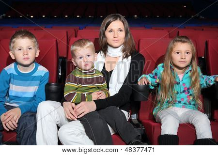 Mother with two sons and daughter watching a movie in the cinema