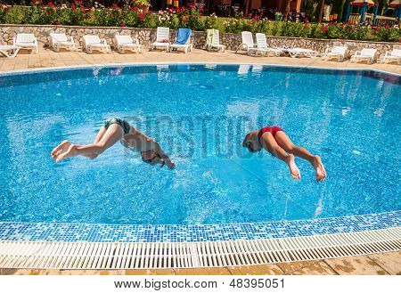 Two Boys Diving Into A Pool