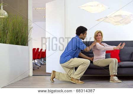 Physiotherapist makes a house call to consult with a middle aged woman, suffering from lower back pains, at her place of work poster