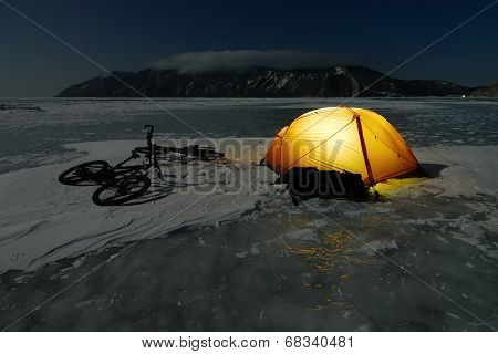 Bicycle tourists' winter camp - orange tent and bikes on the surface of frozen lake. Night scene poster