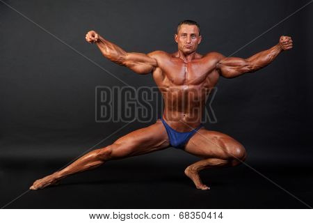 Bodybuilder Posing On Dark Background.