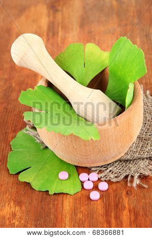 Ginkgo biloba leaves in mortar and pills on wooden background