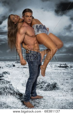 Hunky male with no shirt carrying sexy female model with nice legs