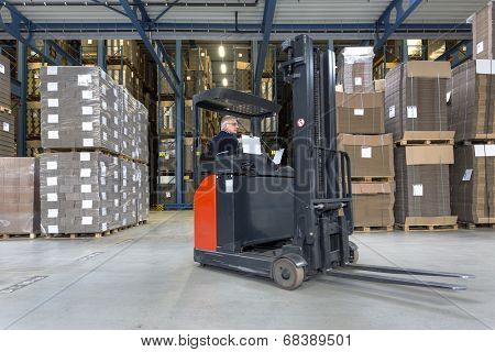 Reach truck driving around cartboard boxes in a warehouse.