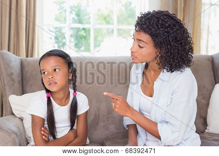 Pretty mother sitting on couch scolding her daughter at home in the living room