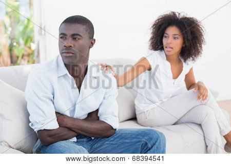 Attractive couple having an argument on couch at home in the living room poster