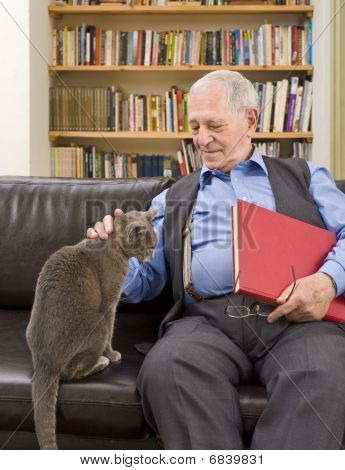 senior man with book at home caressing a cat on the sofa poster