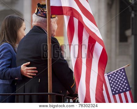 NEW YORK - NOV 11, 2014: An older US vet on a parade float holds an American Flag in the 2014 America's Parade held on Veterans Day in New York City on November 11, 2014.