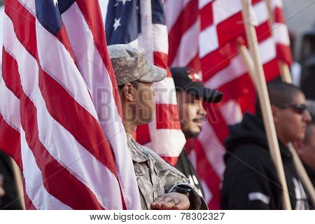NEW YORK - NOV 11, 2014: US vets carry American Flags as they march in the 2014 America's Parade held on Veterans Day in New York City on November 11, 2014.