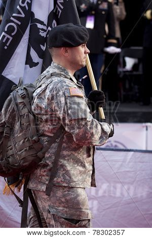 NEW YORK - NOV 11, 2014: A US vet in uniform carries the black and white Wounded Warrior Project flag as he marches in the 2014 America's Parade on Veterans Day in New York City on November 11, 2014.