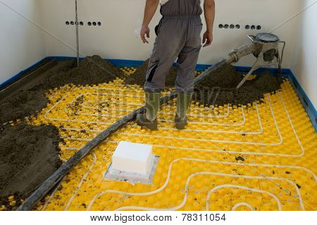 Plasterer at indoor concrete cement floor topping with float poster