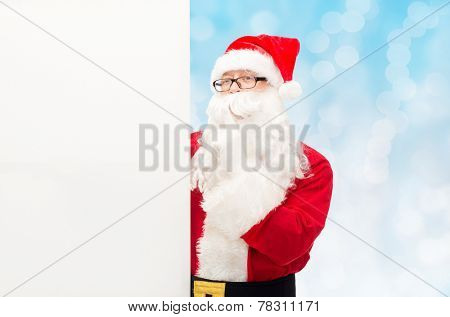 christmas, holidays, advertisement and people concept - man in costume of santa claus with white blank billboard making hust gesture over blue lights background