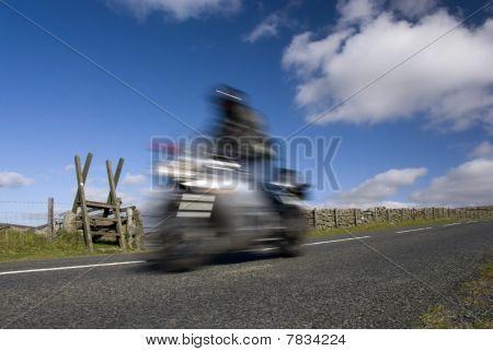 Blurred Speeding Motorbike On Mountain Road