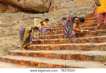 :Hindu devotees apply kumkuma to the temple steps during annual event Bonalu festival