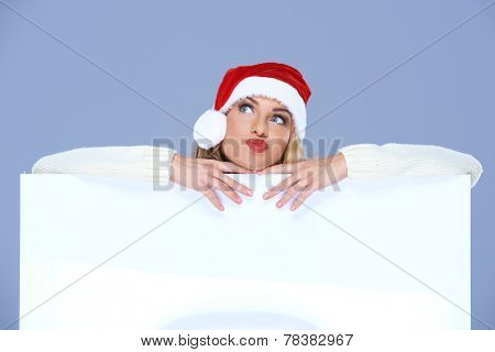 Attractive young blond woman wearing a festive red Santa hat pulling a quizzical expression as she leans on a blank white placard or sign with copyspace for your Christmas text  on blue