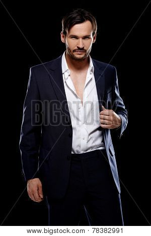 Handsome suave young man in a stylish tailored suit posing with his jacket unbuttoned giving the camera a seductive look on a dark background