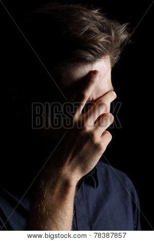 Worried Or Embarrassed Man On Black
