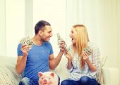 love, family, finance, money and happiness concpet - smiling couple with money and piggybank ot table at home poster