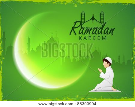 Cute Muslim boy reading Namaz (Islamic Prayer) and beautiful crescent moon on mosque silhouette background for Ramadan Kareem celebration.