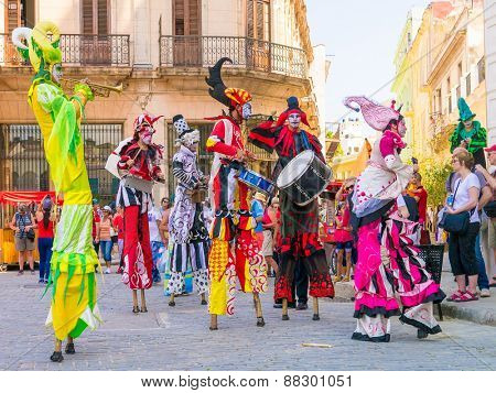 HAVANA, CUBA - APRIL 15,2015 : Colorful stiltwalkers dancing to the sound of cuban music in Old Havana