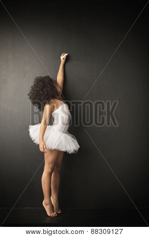 Young ballerina wiritting on blackboard
