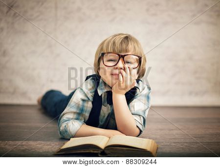 Cheerful smiling little kid reading a book