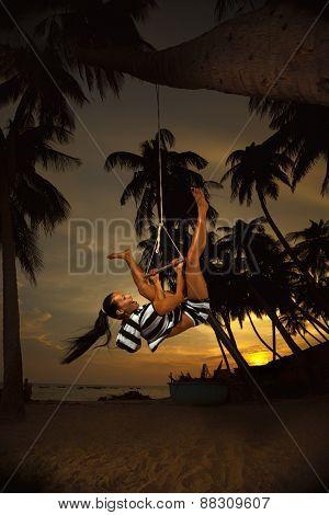 Beautiful girl on the swing on the beach