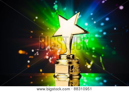 gold star trophy against rainbow sparks background
