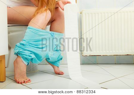 Woman Sitting On Toilet In Morning