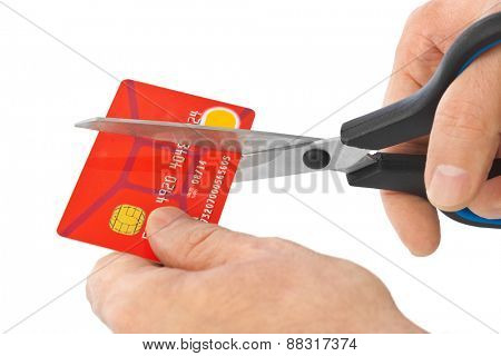 Scissors cutting old credit card isolated on white background