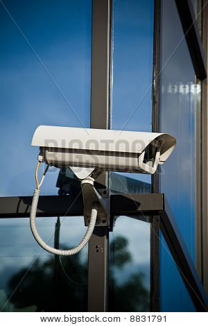 Security Camera Attached On Business Building With Reflections