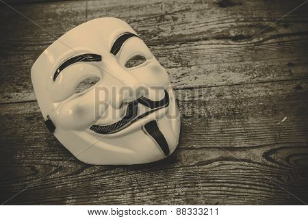 white anonymous mask on wood background - retro style