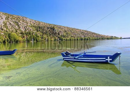 Blue Traditional Old Wooden Fishing Boat With Greece Flag In The Lake Orestiada
