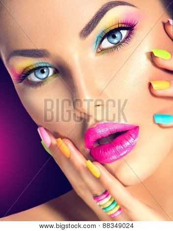 Beauty Girl face with Vivid Makeup and colorful Nail polish. Colourful nails. Fashion Woman portrait close up. Bright Colors. Blue eyes, long eyelashes, vivid eyeshadows Rainbow make up