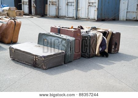 Several Old Suitcases Clothes Are On Asphalt.
