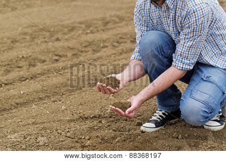 Male Farmer Examines Soil Quality on Fertile Agricultural Farm Land Agronomist Checking Soil in Hands. poster