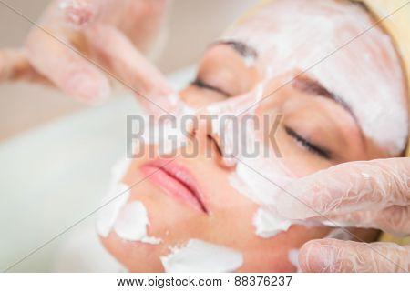 Beautiful woman with facial mask at beauty salon.
