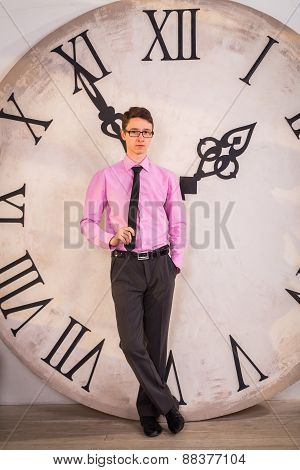 Young man standing near the big clock. A man holding a white sheet of paper.