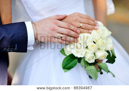hands of the bride and groom on a white wedding bouquet