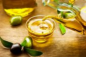 Olive Oil. Bottle pouring Virgin Olive Oil in a bowl close up. Olives and Healthy Olive oil being poured from glass bottle. Diet. Dieting concept. Healthy food poster