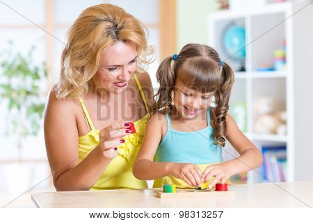 kid with mother playing together at table