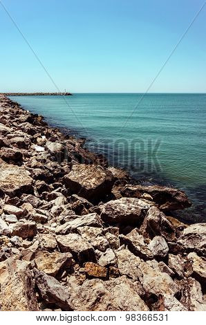 Brown Stones Wall Around Small Harbor With Lighthouse In Greece