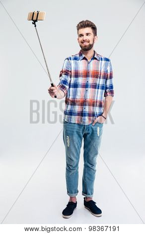 Full length portrait of a smiling man making selfie photo with stick isolated on a white background