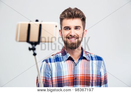 Portrait of a cheerful young man making selfie photo with stick isolated on a white background