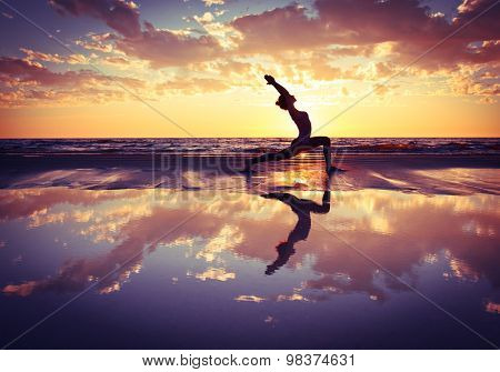 silhouette of woman practicing yoga on the beach at sunset