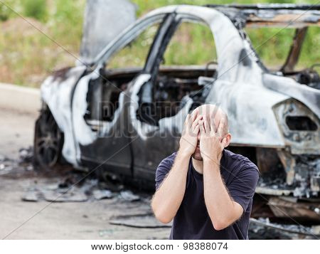 Crying upset caucasian man at road wreck accident or arson fire burnt wheel car vehicle junk