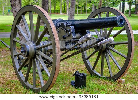 A civil war cannon with large wheels and a bucket for wads. poster