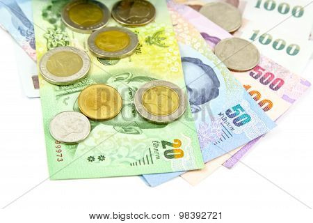 Many of Thai Baht Coins and banknote on white background